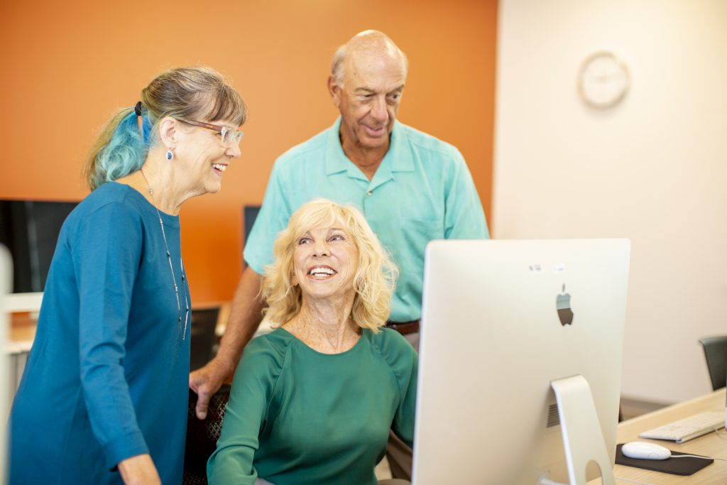 3 people viewing something on a computer screen